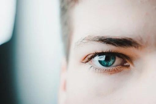 foto detalhe mostra olho e sobrancelha marcada e bem feita de uma moça de olhos verdes